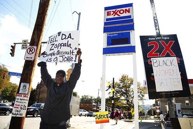 A protester holds up a sign calling out District Attorney Stephen Zappala outside the Exxon gas station in Marshall-Shadeland. - CP PHOTO: JARED WICKERHAM