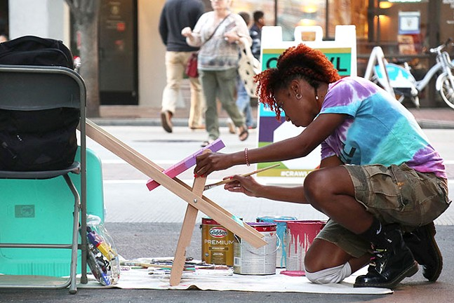 """Janel Young paints a chair for VisitPittsburgh's """"Pull Up a Chair"""" project. - CP PHOTO: JOIE KNOUSE"""