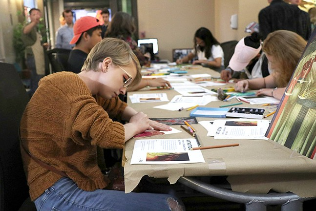 Emily Besselman, a student at the University of Pittsburgh, draws at a table set up inside the Catholic Charities Diocese of Pittsburgh. - CP PHOTO: JOIE KNOUSE