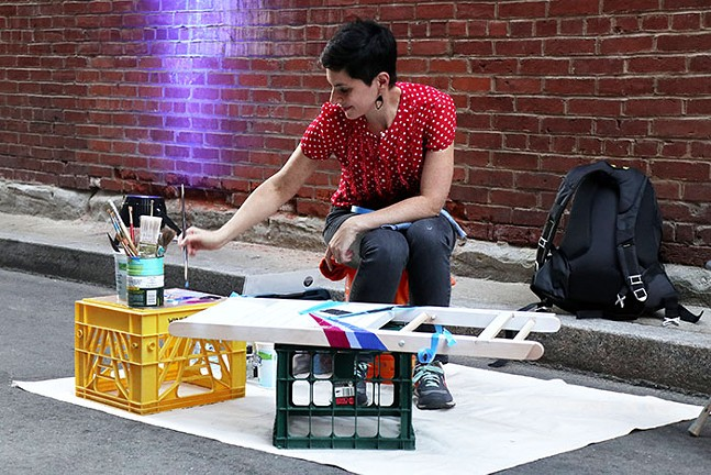 """Lauren Brawn paints a chair for VisitPittsburgh's """"Pull Up a Chair"""" project. - CP PHOTO: JOIE KNOUSE"""