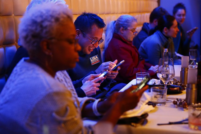 Supporters check their cell phones for the latest election results. - CP PHOTO: JARED WICKERHAM