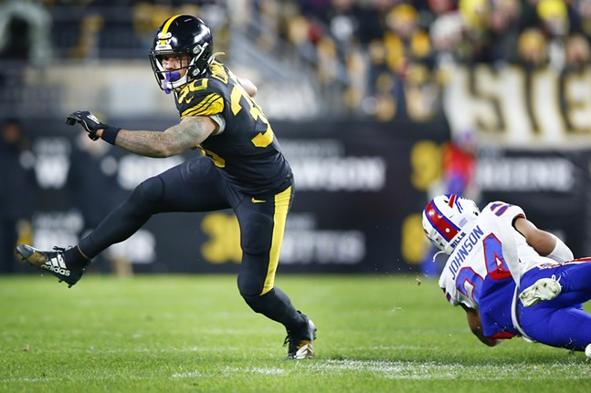 James Conner #30 of the Pittsburgh Steelers avoids a tackle by Taron Johnson #24 of the Buffalo Bills. - CP PHOTO: JARED WICKERHAM