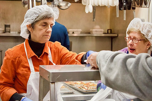 A volunteer hands out meals at Light of Life Rescue Mission in the North Side - CP PHOTO: JOIE KNOUSE
