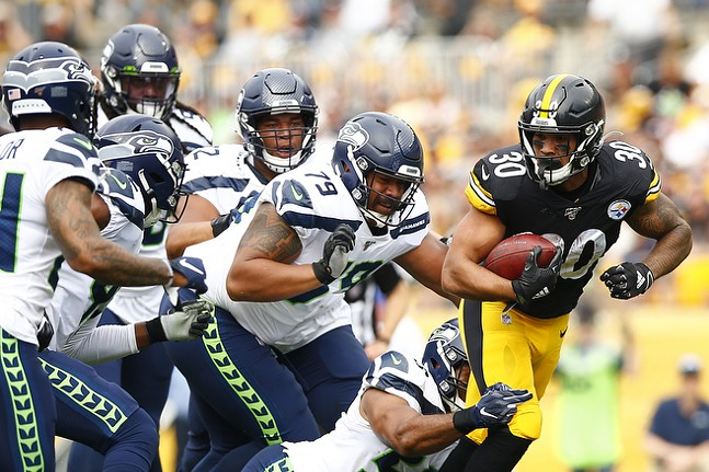 James Conner #30 of the Pittsburgh Steelers carries the ball against the Seattle Seahawks defense. - CP PHOTO: JARED WICKERHAM