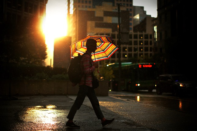 A pedestrian walks with an umbrella as the sun shines inbetween rain showers downtown. - CP PHOTO: JARED WICKERHAM