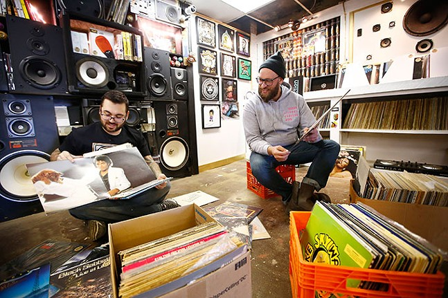 T.J. Harris, owner of The DJ Connection, and Josh Snider, owner of Flower City Printmakers, look through boxes of records inside their Bridgeville location. - CP PHOTO: JARED WICKERHAM