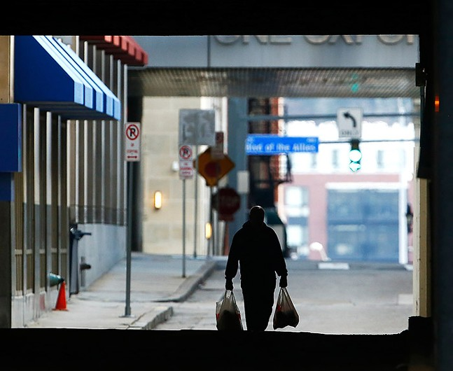 A man carries shopping bags in Downtown Pittsburgh on Sun., March 15 - CP PHOTO: JARED WICKERHAM