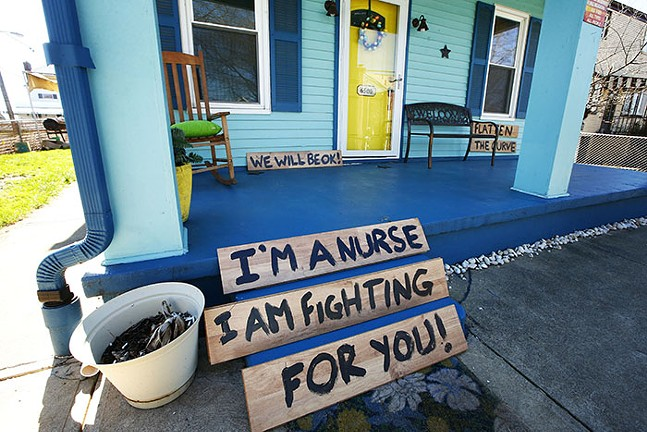 """Signs on a front porch in Stanton Heights read, """"Flatten the curve"""" and """"I'm a nurse. I am fighting for you! We will be OK!"""" - C"""