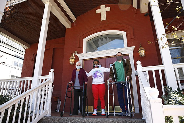 Emmaus Community of Pittsburgh direct support professional, Michelle Flewellen (center), and two residents, Gerry Snow (left) and Kevin Kareis (right), pose for a portrait on the front porch of their home on Mon., April 20, 2020. Emmaus Community of Pittsburgh is a non-profit that provides homes and support for people with intellectual disabilities. - CP PHOTO: JARED WICKERHAM