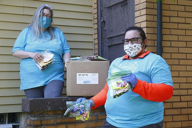 Sue Kerr, of Pittsburgh Lesbian Correspondents, and Allison Butka, of Etna Print Circus, pose for a portrait with masks they are donating to the LGBTQ community on Wed., May 13 in Etna, Pa. - CP PHOTO: JARED WICKERHAM