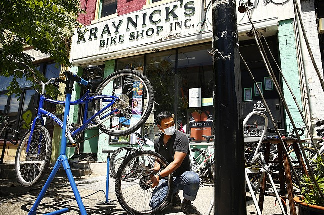 Rocky Cristobal, owner of Kraynick's Bike Shop, repairs bikes outside on the sidewalk in Garfield on Thu., May 21, 2020. - CP PHOTO: JARED WICKERHAM