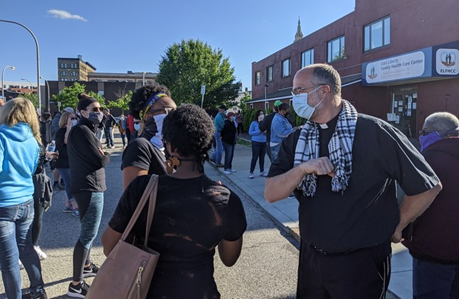 Pastor Paul Roberts (right) of Eastminster Presbyterian Church bumps elbows with two worshipers on May 31, 2020. - CP PHOTO: AMANDA WALTZ