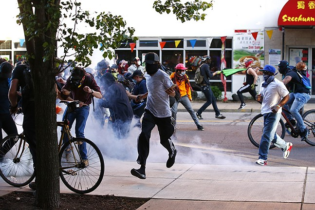Crowd dispersing on Centre Avenue after canisters of tear gas or tear smoke fired into crowd - CP PHOTO: JARED WICKERHAM