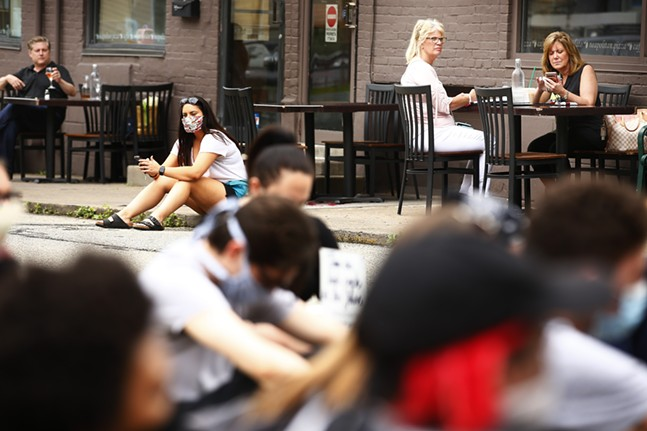 Diners eating on the patio at Mercurio's look on as protesters stage a sit-in along Walnut Street in the Shadyside neighborhood. - CP PHOTO: JARED WICKERHAM