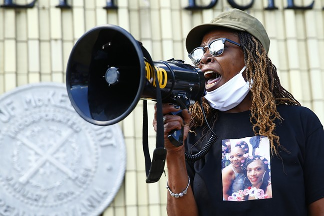 Tonya Reed, the mother of Aaliyah Johnson, screams for answers through the megaphone in front of the police station in downtown McKeesport. - CP PHOTO: JARED WICKERHAM