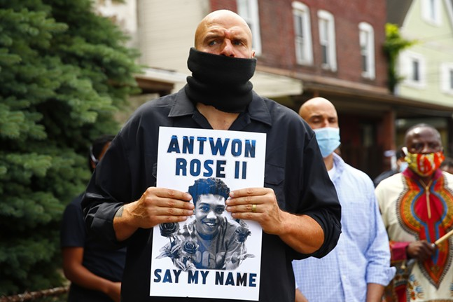 Lt. Governor John Fetterman holds a sign in memory of Antwon Rose II. - CP PHOTO: JARED WICKERHAM