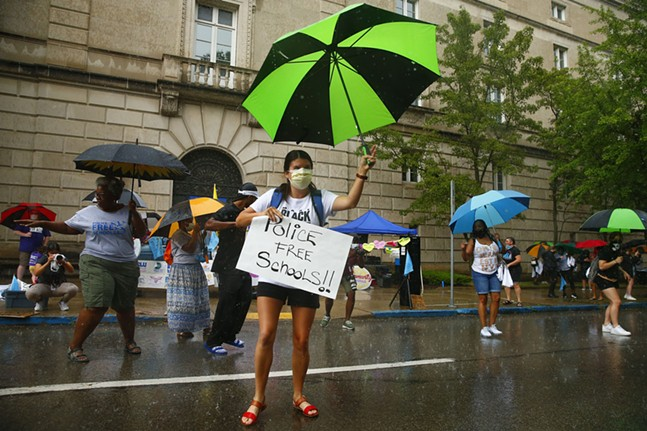 Protesters dance in the pouring rain as they demand police be removed from Pittsburgh Public Schools. - CP PHOTO: JARED WICKERHAM