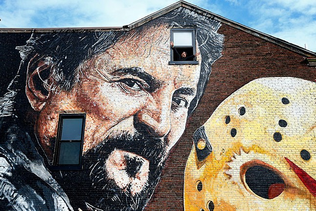 Tom Savini poses in the third-floor window of the house with his mural - CP PHOTO: JARED WICKERHAM