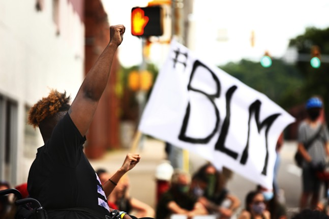 A protester in a wheelchair raises their fist as a Black Lives Matter flag waves in the background. - CP PHOTO: JARED WICKERHAM