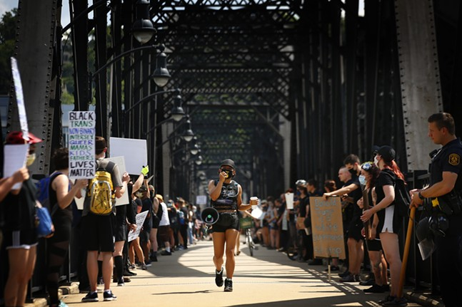 Jalina McClarin leads chants as she marches down the Hot Metal Bridge walkway amidst a line of both protesters and Pittsburgh police officers. - CP PHOTO: JARED WICKERHAM