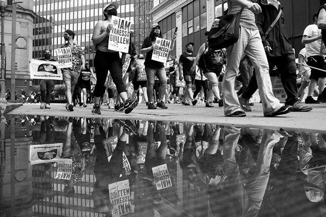 Protesters are reflected in a puddle following a short thunderstorm in the Cultural District. - CP PHOTO: JARED WICKERHAM