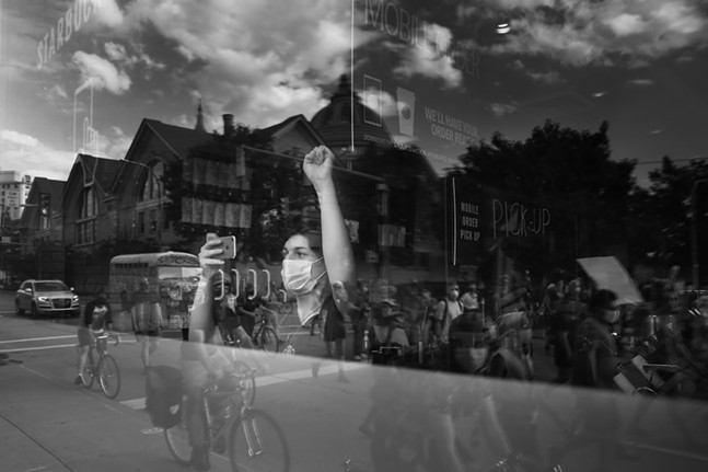 A Starbucks employee raises their fist as protesters march along Centre Avenue. - CP PHOTO: JARED WICKERHAM