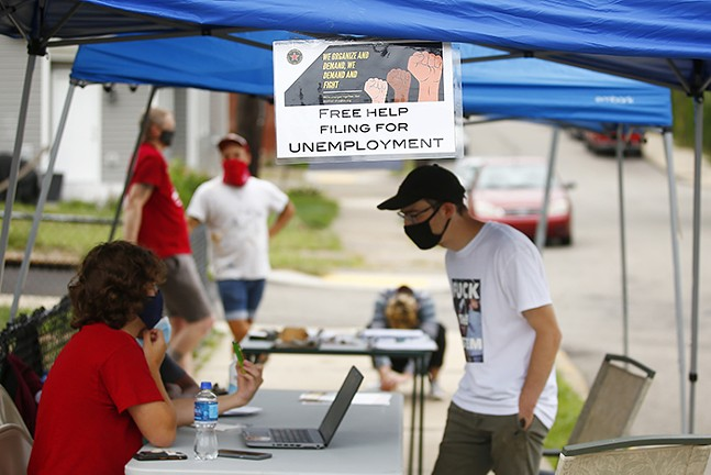 Members of Pittsburgh Unemployed Council help people from the community file various paperwork near Nelson Mandela Park in Garfield on Sat., Aug. 15, 2020. - CP PHOTO: JARED WICKERHAM