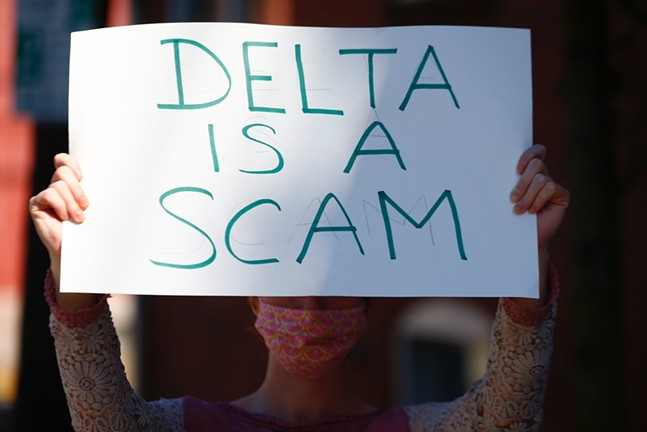 A protester holds up a sign against the Delta Foundation on the South Side. - CP PHOTO: JARED WICKERHAM