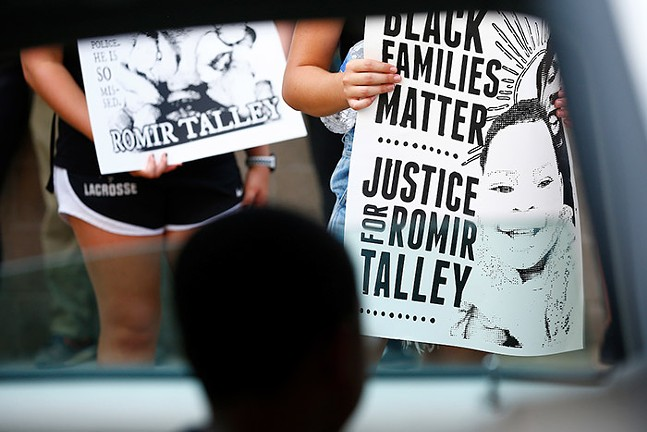 The son of Romir Talley looks out of a car and at signs carried by protesters at a rally for his father in Wilkinsburg on Sat., Aug. 22, 2020. - CP PHOTO: JARED WICKERHAM