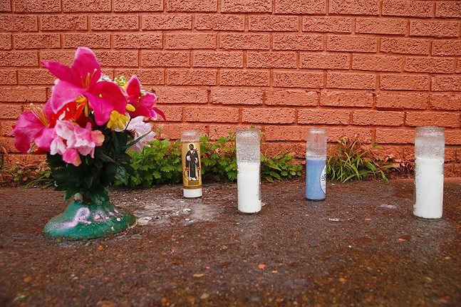 Flowers and candles left in front of a painted-over Ramir Talley mural in Wilkinsburg - CP PHOTO: JARED WICKERHAM