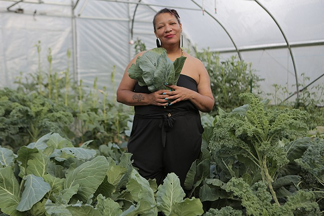 """Raqueeb Bey stands inside the Homewood Community Historic Farm's greenhouse, referred to as """"The Green Trap House."""" - PHOTO: BRIAN COOK"""