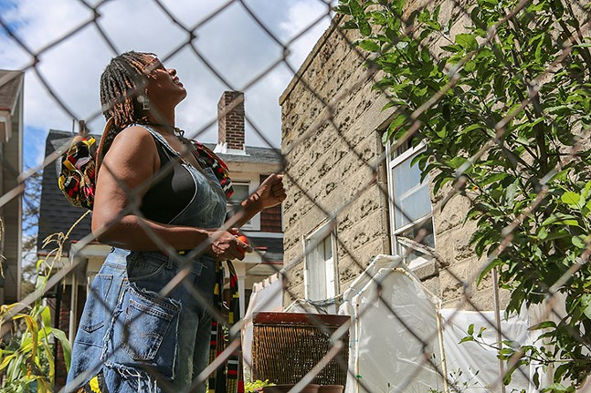 Ebony Lunsford-Evans, owner of FarmerGirlEB, monitors the health of her apple tree, moments - after picking the remaining green apples. - PHOTO: BRIAN COOK