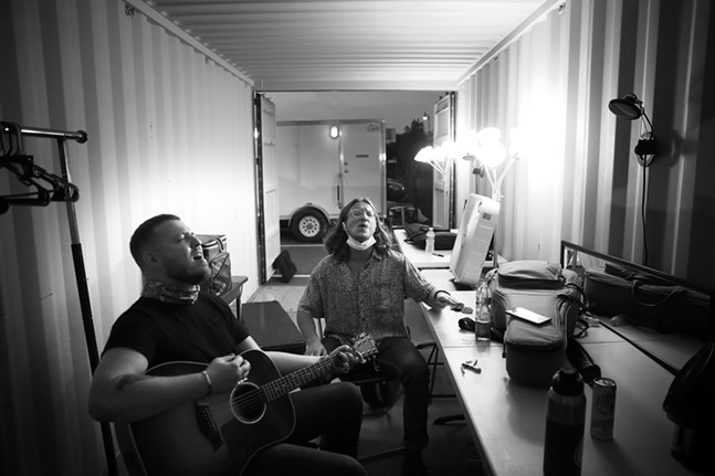 Nick Guckert (left) and Edward Angelo (right) of The Living Street warm up inside of their shipping container in the parking lot of Hazelwood Green before going on stage. - CP PHOTO: JARED WICKERHAM