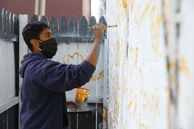 Zim Syed, lead artist on the John Lewis mural, paints on Sun., Oct. 4. - CP PHOTO: JARED WICKERHAM