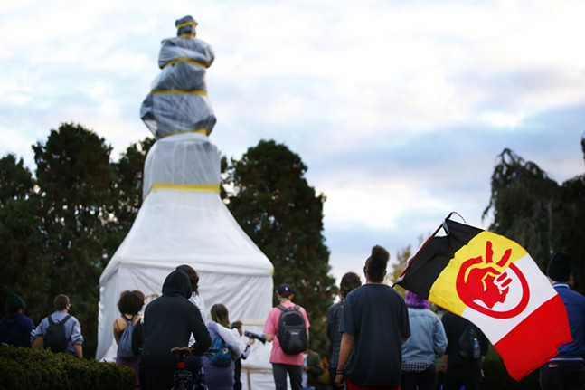 Emmanuel Todd-Baraka, carrying an American Indian Movement flag, listens to speakers during a protest on Indigenous Peoples' Day in front of the wrapped-up Christopher Columbus statue in Oakland. - CP PHOTO: JARED WICKERHAM