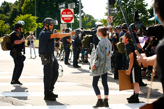 A Pittsburgh Police officer in riot gear threatens a protester with pepper spray during a demonstration in Downtown Pittsburgh on Sat., July 4, 2020. - CP PHOTO: JARED WICKERHAM