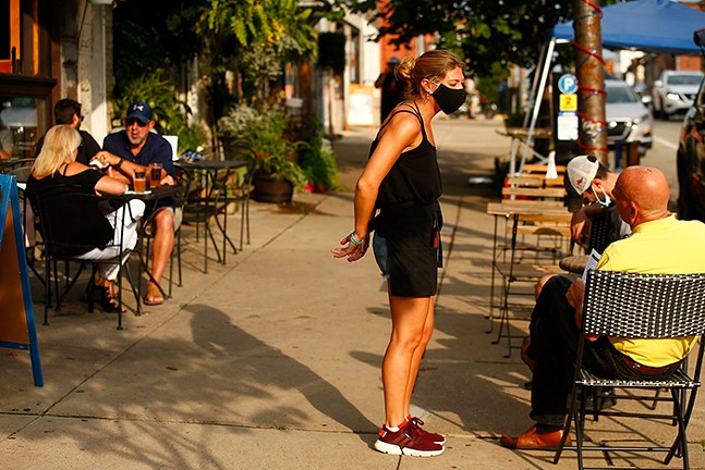 A server waits on tables outside of Lot 17 in Bloomfield in July - CP PHOTO: JARED WICKERHAM