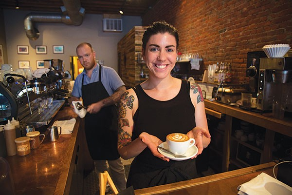 Emily Hurley shows off a caffeinated work of art made by Braden Walter Jr. (background). - PHOTO BY THEO SWARTZ