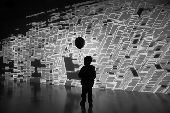 Sol Ksiazkiewicz, 4, carries his balloon through the Power Pixels 2020 installation by Miguel Chevalier at Wood Street Galleries during the gallery crawl on Fri., Jan. 24, 2020. - CP PHOTO: JARED WICKERHAM