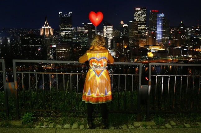 Jena-Anne Sabon, an organizer of #LovefromPgh, stands atop Mount Washington with a lighted heart and a decorated jacket during 'Illumination-Ovation' on Tue., April 7, 2020. - CP PHOTO: JARED WICKERHAM