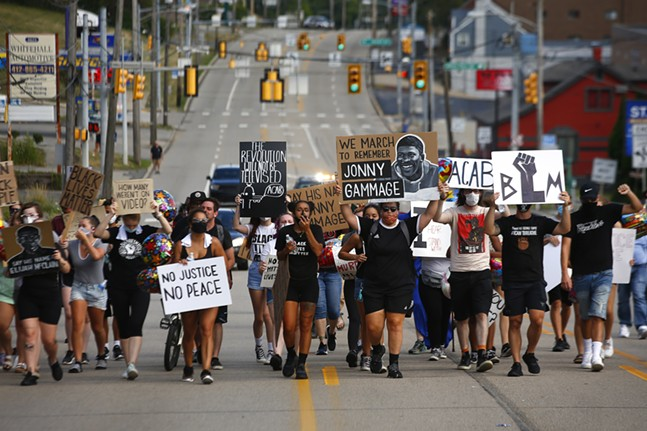 Protest organizer Camille Redman leads the group as they march through Brentwood from the Giant Eagle along Route 51 in honor of Jonny Gammage on his birthday, who was killed by police in 1995, on Mon., July 20, 2020. - CP PHOTO: JARED WICKERHAM
