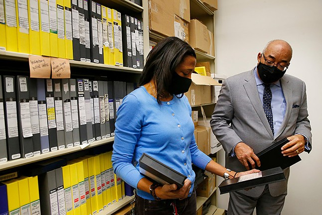 Minette Seate and Chris Moore look at archived tapes inside the WQED tape vault room. - CP PHOTO: JARED WICKERHAM