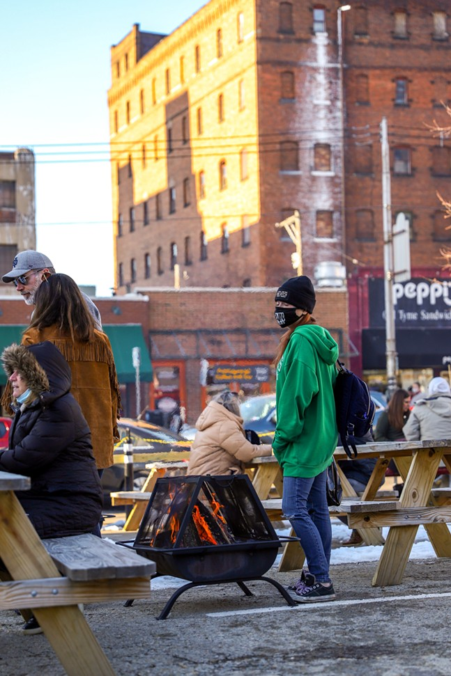 People enjoy the warmth of the fire outside of 1700 Penn Avenue. - CP PHOTO: KAYCEE ORWIG