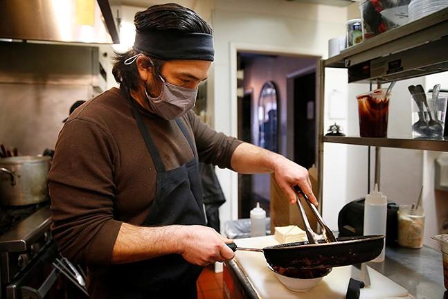 Owner and chef, Simon Chough, prepares the Killer Tofu dish at Soju - CP PHOTO: JARED WICKERHAM