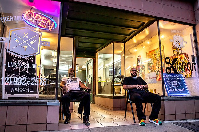 Barbers Bobby Fletcher and Brandon Potts watch the action on East Carson Street from outside unisex salon Trending Styles in Pittsburgh's South Side on Sat., April 10, 2021. - CP PHOTO: KAYCEE ORWIG