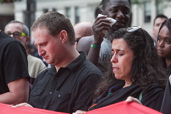 Mourners bow their heads during the reading of the names of those killed in the Orlando shooting. Pittsburgh resident Milton Sibanda (background) reacts to what he believes to be his friend's name listed among the victims. - PHOTO BY JOHN COLOMBO