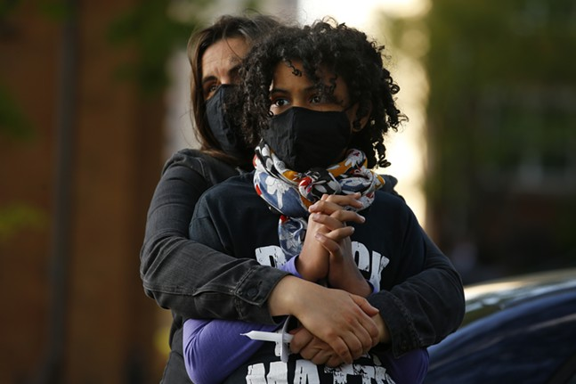 Holly Hickling holds her daughter, Nzinzi Tembo, as protesters speak before marching from Freedom Corner. - CP PHOTO: JARED WICKERHAM
