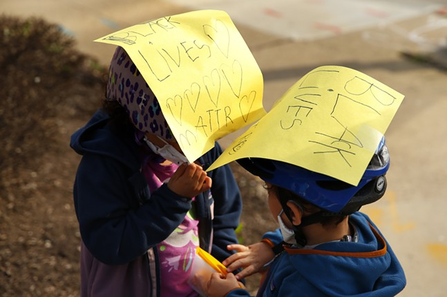Sylvie, 6, and Eli, 4, share snacks while wearing signs on their bicycle helmets before protesters march. - CP PHOTO: JARED WICKERHAM