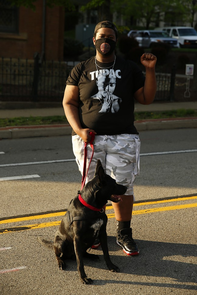 Tae J and his dog Shadow pose for a portrait before protesters march from Freedom Corner. - CP PHOTO: JARED WICKERHAM