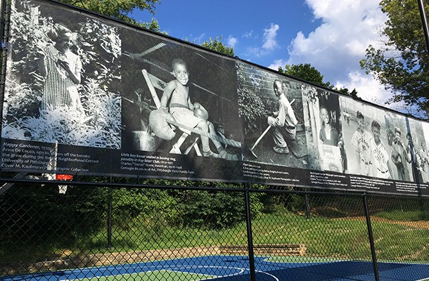 Teenie Harris photos displayed along the fence by the park's half basketball court - PHOTO COURTESY OF SCOTT ROLLER/PITTSBURGH PARKS CONSERVANCY